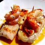 Lomos de merluza con langostinos sobre cama de mostaza y aceite extra virgen